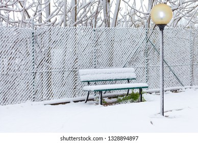 Empty Bench in a playground after snowfall in Rome