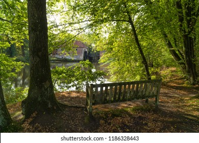 empty bench at a pond with a water mill