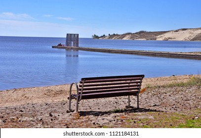 Empty bench for resting in Nida, resort town near Curonian Spit, Lithuania, Baltics. Relaxation. Parnidis Dune in Nida in the background.