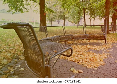 Empty benches in the park with fallen leaves on the ground in autumn. Vintage Style.
