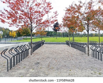 The empty bicycle racks in bicycle parking facility at Sam Eyde school, Arendal city. Norway. Empty place for a parking of bicycles with small stone floor and the green grass on the background.