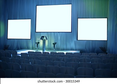 Empty big conference hall with podium and three screens