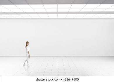 Empty big hall wall mockup. Woman walk in museum gallery with blank wall. White clear stand mock up lobby. Display artwork presentation. Art design empty floor. Expo studio  loft corridor.