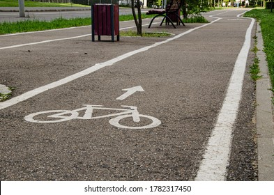 Empty bike path along the roadway. In the foreground is a sign on the asphalt
