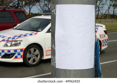 Empty bill poster on light pole with police squad car in the background.