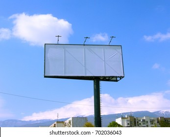 An empty billboard in the city, on a blue sky background, buildings and view to the mountain