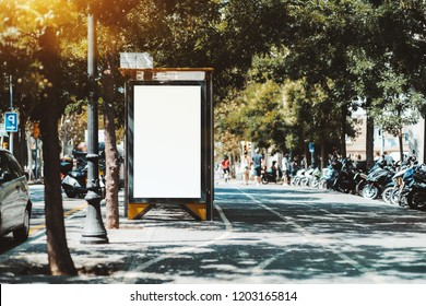 Empty billboard placeholder template on the city bus stop with the sidewalk on the right; blank advertising banner mock-up near the road with mopeds; white empty informational signboard on the street