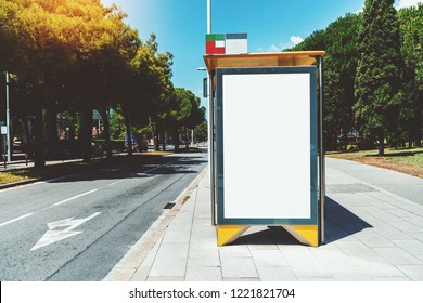 Empty billboard placeholder template on an urban bus stop with the sidewalk on the left; blank advertising banner mock-up in city settings; white empty informational signboard near the highway