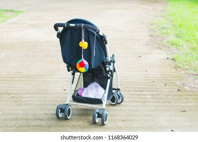 Empty black baby stroller in a park - Missing child concept, perambulator