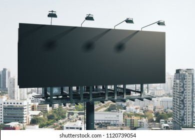 Empty black billboard on bright city background. Retail, advertisement and commerce concept. Mock up, 3D Rendering