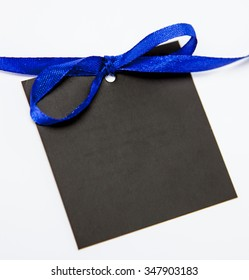 Empty black card with bow on white background