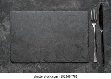 empty black granite stone rectangle board with fork and knife on black textured cement background, top view vith copy space for your text