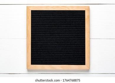 Empty black letterboard on white wood background. Design mockup