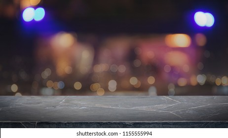Empty black marble stone table top on abstract blurred restaurant and nightclub lights background - can be used for display or montage your products