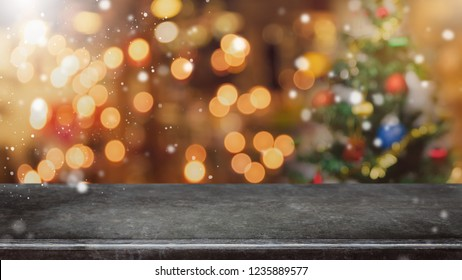 Empty black marble stone table top with bokeh light on blurred Christmas tree banner background with snowfall - can be used for display or montage your products.