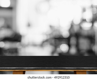 Empty black marble table top with leg with black and white people siting at cafe blurred background,Mock up scene for display or montage of product.