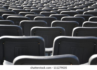 empty black plastic chairs alligned in many rows