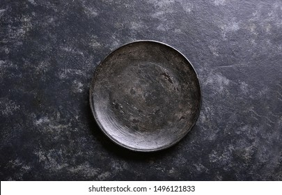 Empty black plate over dark stone background with free space. Top view, flat lay