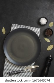 Empty black slate plate on black stone table and napkin. Food background for menu, recipe. Table setting. Flatlay, top view. Mockup for restaurant dish