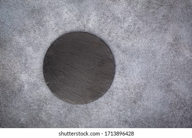 Empty black slate round platter on gray stone background, top view with copy space.