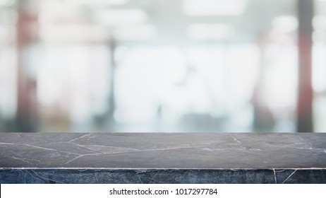 Empty black stone marble table top and blurred abstract background from interior office building background - can used for display or montage your products.