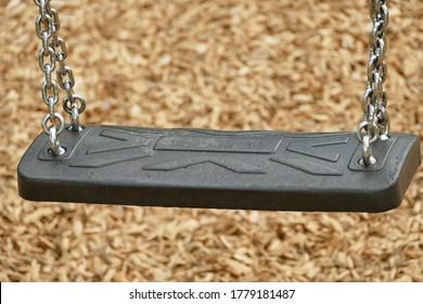 Leere schwarze Swing auf einem modernen Spielplatz