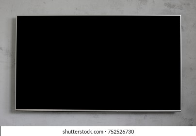 Empty black television screen on concrete wall