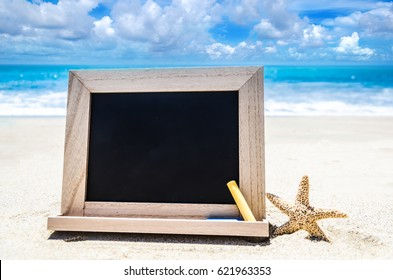 Empty black wood board with chalk and starfish on the sandy beach near the ocean