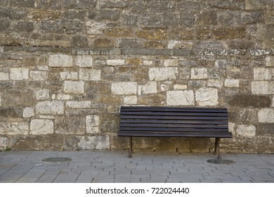 empty black wooden bench against stone background