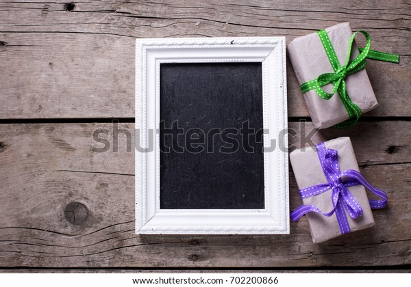 Empty blackboard and  festive gift boxes with presents  on aged  wooden background. Selective focus is on tag. Place for text. Top view. Vertical image.