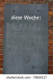 "empty blackboard with the headline ""this week"" in german"