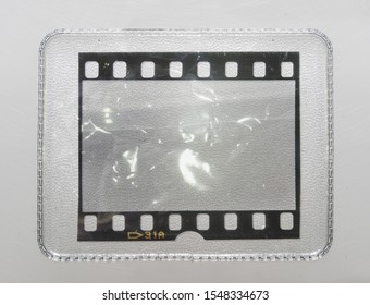 empty or blank 35mm filmstrip behind collector's plastic holder on white background with scratches, trading card holder with film snip in it, just blend in your content here, cool placeholder