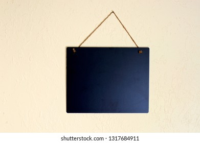 An empty blank black chalkboard hanging on a wall  with rope indoors with copy space.