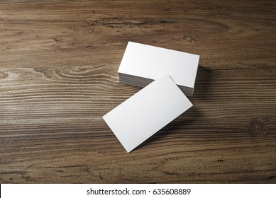 Empty blank business cards on wood table background.