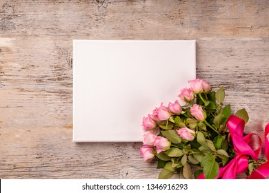 Empty, blank card with rose flower bouquet on wood background