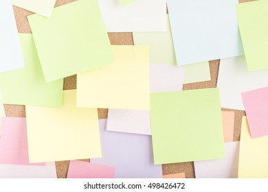 Empty blank sticky notes on notice board in office. Background or backdrop for business information. Concept image of communication or reminder with copy space.