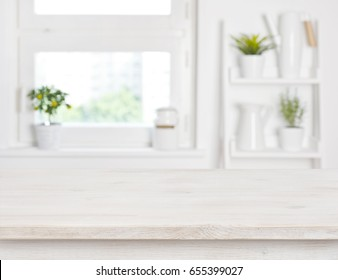 Empty bleached wooden table and kitchen window shelves blurred background