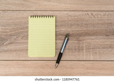 an empty block and a pen on the wooden table