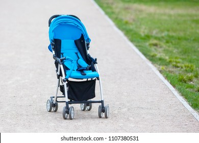 Empty blue baby stroller in a park - Missing child concept