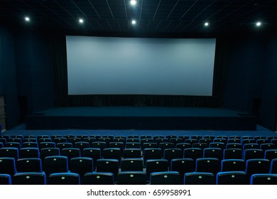 Empty blue cinema hall with white screen and seats.