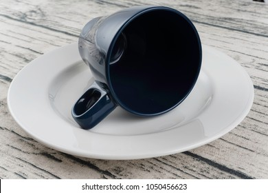 empty blue cup and white plate over wooden surface