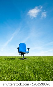 Empty blue fabric office chair standing outdoors in the middle of an empty green field under sunny blue sky