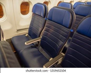 Empty blue leatherette slimline airplane seats in Economy with seatbelts neatly folded before passengers board. Outside the porthole windows airport lights glow orange in the night