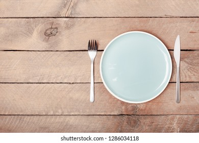 Empty blue pastel colored plate and steel cutlery on grunge wood plank desk with copy space