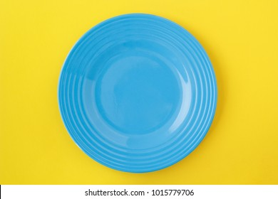Empty blue plate on yellow. From above view.