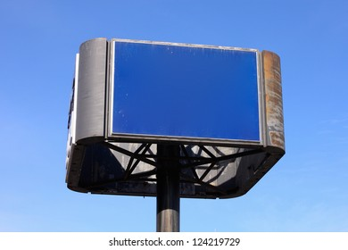 An empty blue sign before a clear blue sky.