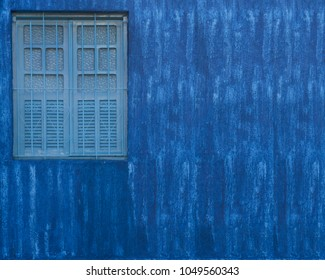 Empty blue wall with small window Detail of house exterior wall.