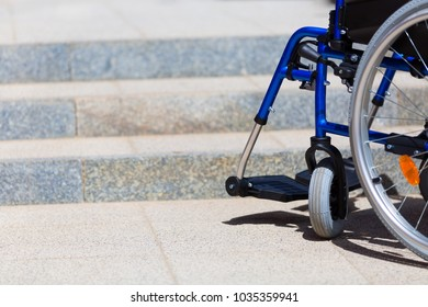 empty blue wheelchair standing before inaccesible steps
