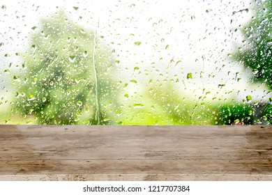 Empty board and abstract background with raindrop and water droplet on window after rain with blurry background blurry  green trees and field, gray clouds and sky,