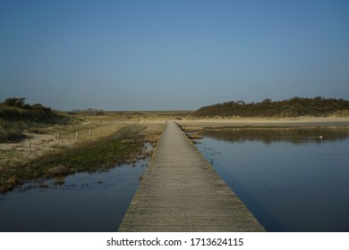 An empty boardwalk over a shallow sound or small bay of the ocean. The sandy dunes have grass and trees on them. Concept of serenity, peace and mindfulness. A place to empty the mind and stop worrying